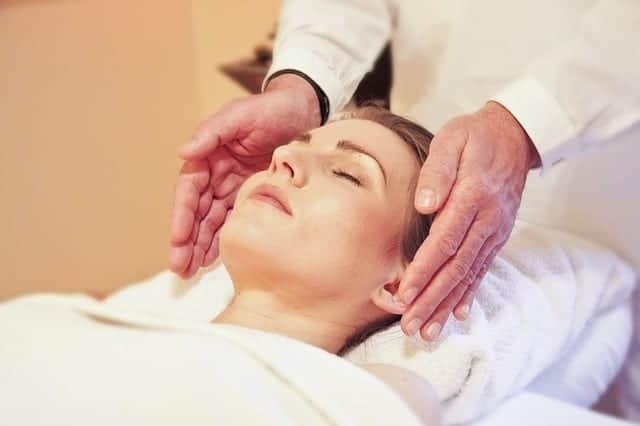 A woman receiving a reiki treatment